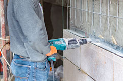 The process of drilling holes in the concrete wall Stock Images