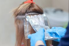Hair dyeing process. Process of dyeing hair at beauty salon. Closeup of dyeing foil in hair royalty free stock images
