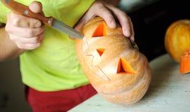 Process för allhelgonaaftonpumpaklipp, process av danandeStålar-nolla-lyktan Manhänder med kniven Arkivfoto
