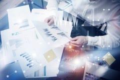 Process för arbete för riskledning Händer för dokument för statistik för fotobankir hållande Använda elektroniska apparater Grafi Arkivfoton
