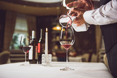 Process of filling glass with wine. Man is pouring red nectar from carafe into goblet that standing at table royalty free stock photo