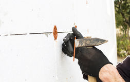The process of fixing the dowel-umbrella with a hammer Stock Image