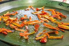 Process of frying roasting slices of red bell peppers capsicums in hot sizzling olive oil. Large flat paella or jambalaya pan Stock Photo