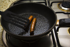 Process of frying sausages 2: rolling sausages to fry Royalty Free Stock Photos