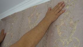 The process of gluing Wallpaper on the wall,the hand of the worker is smooth Wallpapers stock footage