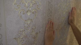 The process of gluing Wallpaper on the wall,the hand of the worker is smooth Wallpapers.  stock footage