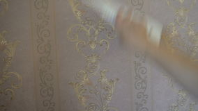 The process of gluing Wallpaper on the wall,the hand of the worker to smooth the Wallpaper with a spatula clamping stock video footage