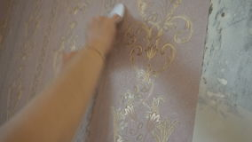 The process of gluing Wallpaper on the wall,the hand of the worker to smooth the Wallpaper with a spatula clamping.  stock video