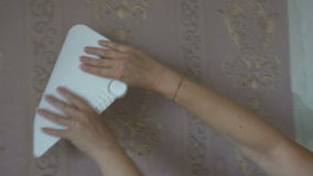 The process of gluing Wallpaper on the wall,the hand of the worker to smooth the Wallpaper with a spatula clamping stock footage
