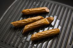 Process of grilling sausages Royalty Free Stock Photos