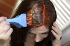 Process of hair coloring at home. Scene in motion. Process of hair coloring at home. Applying red color to your hair. Hair brush in the hand stock image