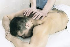 The process of health-improving sports massage is done by a man. The process of health-improving sports massage is done by a men in a medical clinic Stock Images