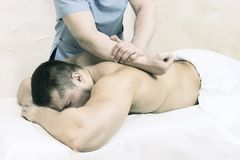 The process of health-improving sports massage is done by a man. The process of health-improving sports massage is done by a men in a medical clinic Stock Photos
