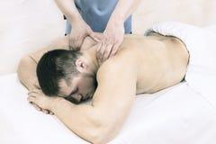 The process of health-improving sports massage is done by a man. The process of health-improving sports massage is done by a men in a medical clinic Stock Photo