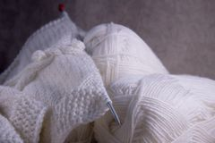 The process of knitting a white wool scarf for a woman. White yarn for knitting and knitting needle stock photography
