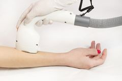 The process of laser depilation of female limbs. In the beauty salon Stock Photos
