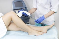 The process of laser depilation of female limbs. In the beauty salon Stock Photo