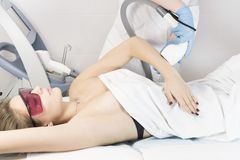 The process of laser depilation of female limbs. In the beauty salon royalty free stock photography