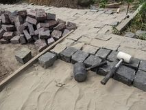 In the process of laying black and red granite pavers stock image