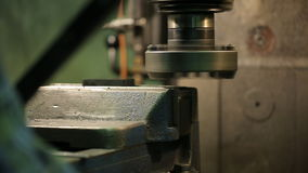 Process of machining metal parts on a vertical milling machine. A vertically disposed spindle, which in some models allows displacement along its axis and stock footage