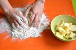 Process of making a dough from farina and butter on orange silicone pad.  Royalty Free Stock Photo