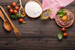 The process of making Food background for tasty Italian dishes with tomato. Various cooking ingredients with spaghetti and spoon. Food background for tasty stock photo