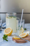 The process of making homemade lemonade. Bright photo of homemade lemonade with fresh mint and lemons stock image