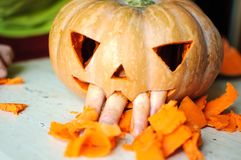 Process of making Jack-o-lantern. Funny picture of Halloween pumpkin monster face with male fingers. Stock Image