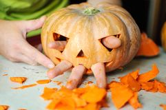 Process of making Jack-o-lantern. Funny picture of Halloween pumpkin monster face with male fingers. Selective focus and bokeh Royalty Free Stock Photo