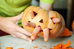 Process of making Jack-o-lantern. Funny picture of Halloween pumpkin monster face with male fingers. Stock Photo