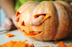 Process of making Jack-o-lantern. Funny picture of Halloween pumpkin monster face with male fingers. Royalty Free Stock Images