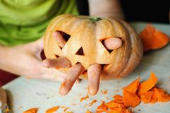 Process of making Jack-o-lantern. Funny picture of Halloween pumpkin monster face with male fingers. Selective focus and bokeh Royalty Free Stock Photography