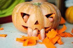Process of making Jack-o-lantern. Funny picture of Halloween pumpkin monster face with male fingers. Stock Photography