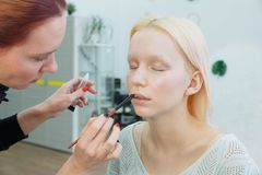 Process of making makeup. Make-up artist working with brush on model face stock photo