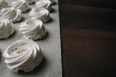 The process of making marshmallow. Close up hands of the chef with confectionery bag cream to parchment paper at pastry shop royalty free stock photos