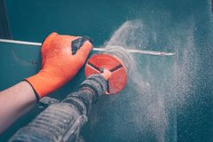 The process of making round holes in gypsum. Board, the rotation of the tool with dust, movement royalty free stock photo