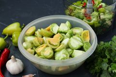 The process of making salad of green tomatoes with pepper, garlic, dill and parsley. Cooking salad of green tomatoes with pepper, garlic, dill and parsley royalty free stock photography