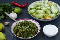 The process of making salad of green tomatoes with pepper, garlic, dill and parsley. In the foreground bowl there is a spicy green sauce. Horizontal photo royalty free stock images