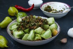 The process of making salad of green tomatoes with pepper, garlic, dill and parsley. Green sauce is added to the tomatoes. Horizontal photo stock photo