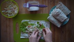 The process of making shawarma with female hands on a wooden table, top view. stock video