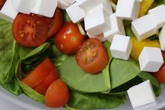 Making Salad with Feta, Tomatoes and Spinach. Process of making some homemade healthy and delicious salad. At this point there is spinach, cherry tomatoes royalty free stock photography