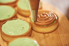 Process of making tart with salted caramel french dessert. Food industry, mass or volume production. Pastry chef making dessert royalty free stock images