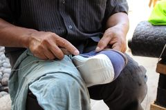 Process of manual shoe reparation, sole and welt fixing and stitching stock photo