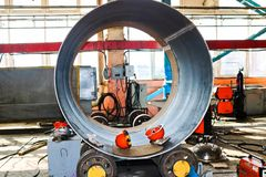 The process of manufacturing a cylindrical body for a container, a heat exchanger on rolls, by rolling, welding and orange helmets stock photo