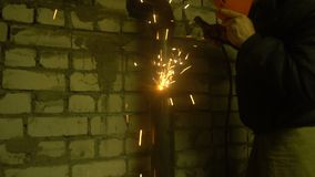 The process of manufacturing a decorative metal product. Metal sparks fly apart from the detail. Welding of metal in the stock video