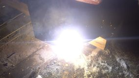 The process of manufacturing a decorative metal product. Metal sparks fly apart from the detail. Welding of metal in the stock video footage