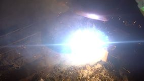 The process of manufacturing a decorative metal product. Metal sparks fly apart from the detail. Welding of metal in the stock footage