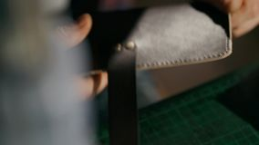 The process of manufacturing a leather wallet handmade. The artisan combines elements with rivets. Handmade leather stock video footage