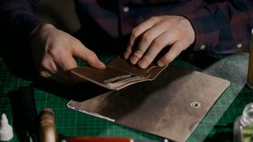 The process of manufacturing a leather wallet handmade. The artisan puts glue on the leather parts of the wallet and stock footage