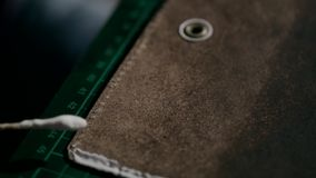 The process of manufacturing a leather wallet handmade. The artisan puts glue on the leather parts of the wallet and stock video